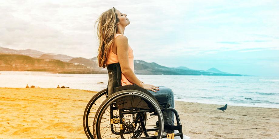 Femme en fauteuil roulant au bord de la mer